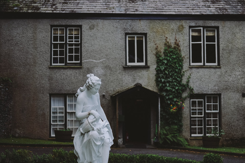 The white stone statue outside Monk Coniston Hall at Julia and Darren's Lake District wedding by Barry Forshaw