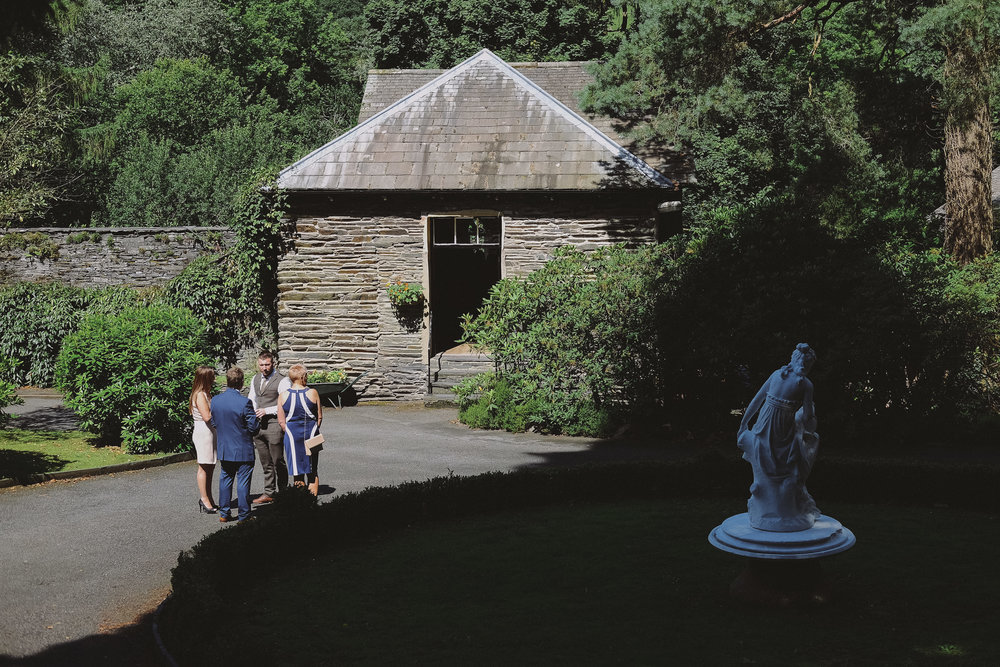 Guests gather outside the slate barn at Julia and Daren's Lake District wedding by Barry Forshaw