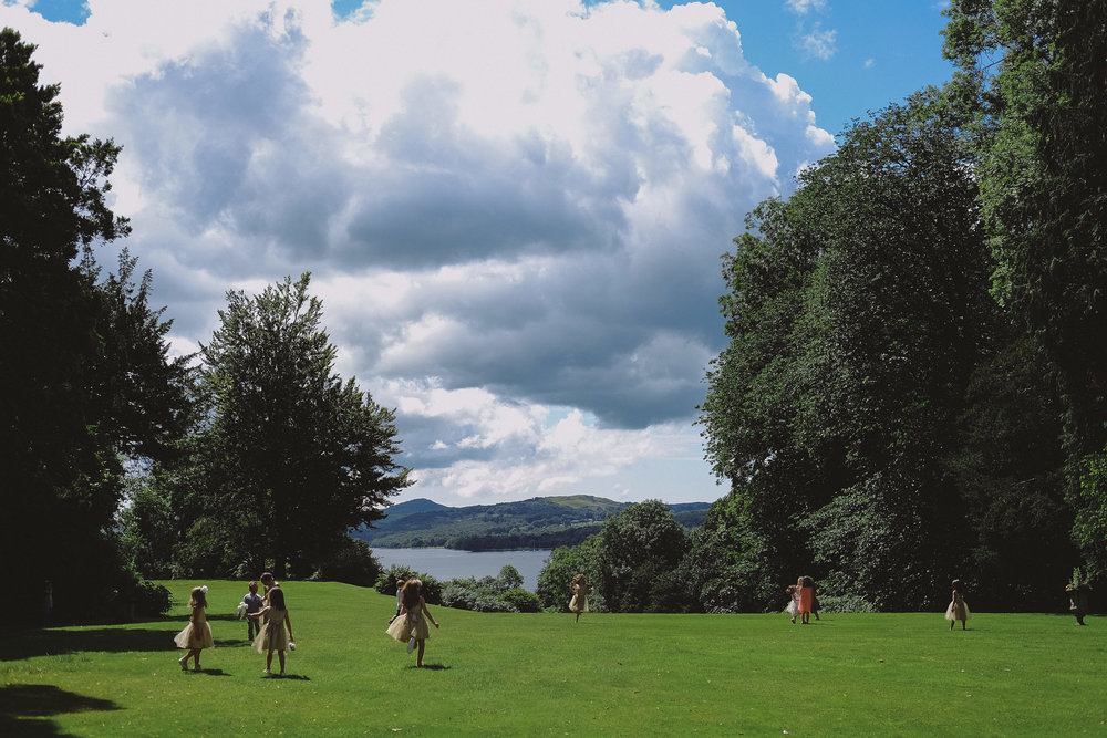 Children play in the grounds of Monk Coniston Hall with Coniston Water in the background at Julia and Darren's Lake District wedding by Barry Forshaw