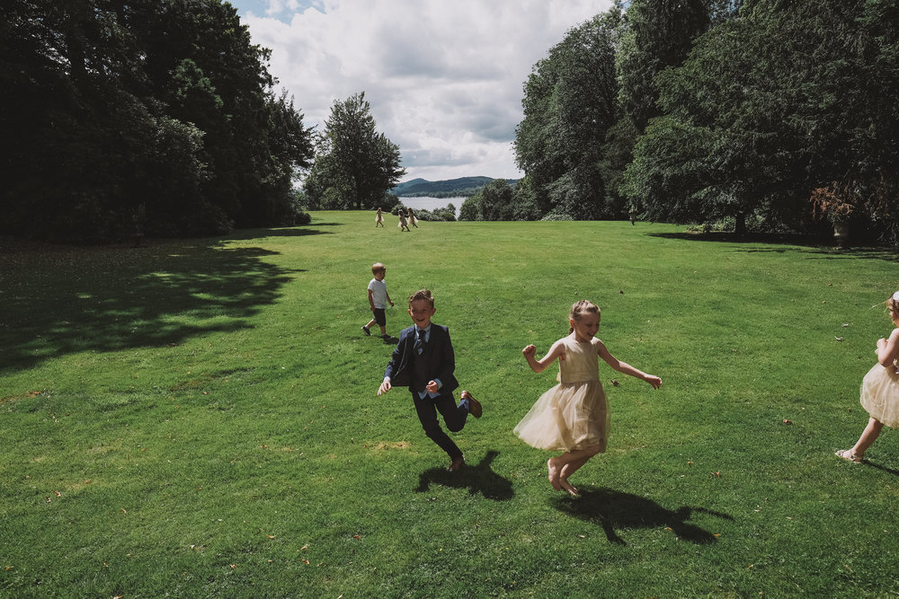 Silly play by children in the grounds of Monk Coniston Hall with Coniston Water in the background at Julia and Darren's Lake District wedding by Barry Forshaw