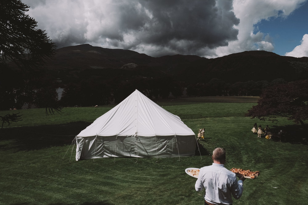 A guest carries food to the marquee at Julia and Darren's Lake District wedding by Barry Forshaw