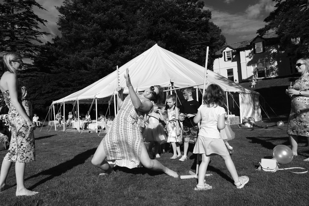 A black and white photo of a guest limbo dancing at Julia and Darren's Lake District wedding by Barry Forshaw