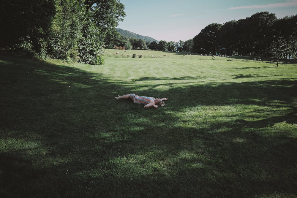 A wedding guest lies on the ground exhausted at Julia and Darren's Lake District wedding by Barry Forshaw