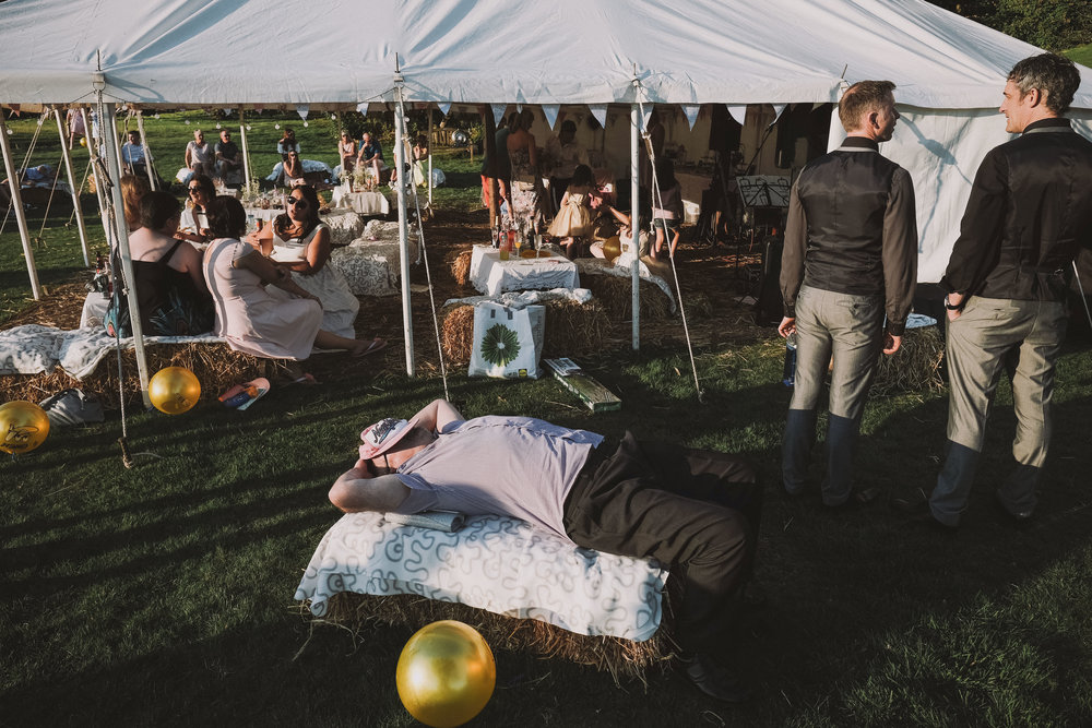 A wedding guest lies asleep on a hay bale at Julia and Darren's Lake District wedding by Barry Forshaw