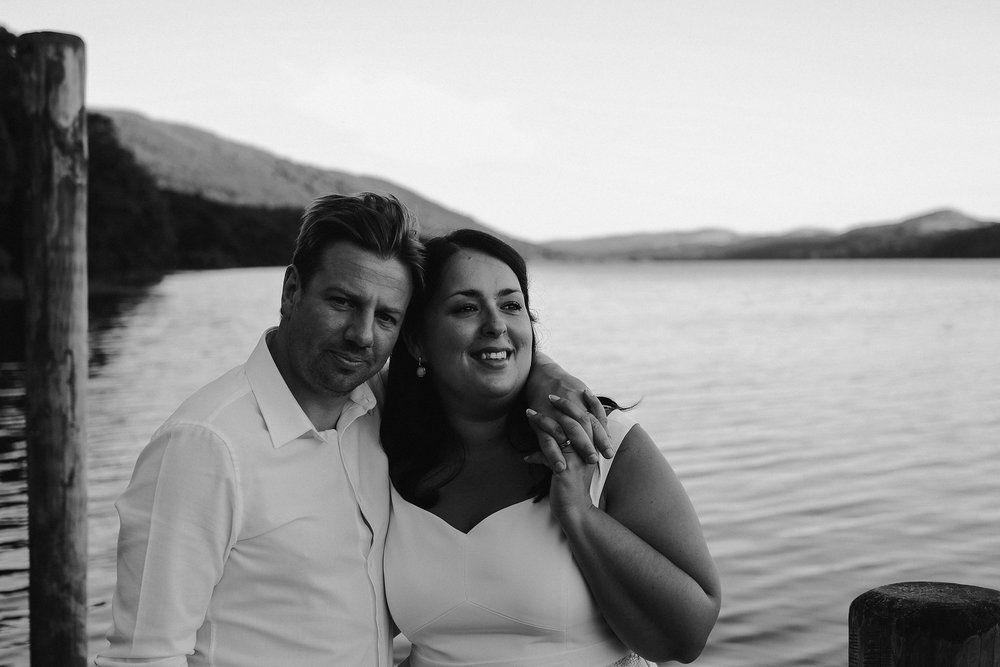 A black and white photo of the bride and groom cuddling on a jetty on Coniston water at Julia and Darren's Lake District wedding by Barry Forshaw
