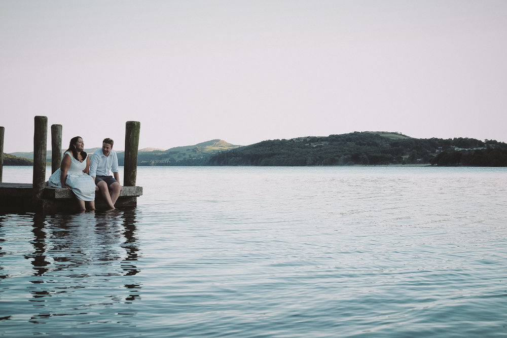 The bride and groom sit on a jetty with their feet in Coniston water at Julia and Darren's Lake District wedding by Barry Forshaw