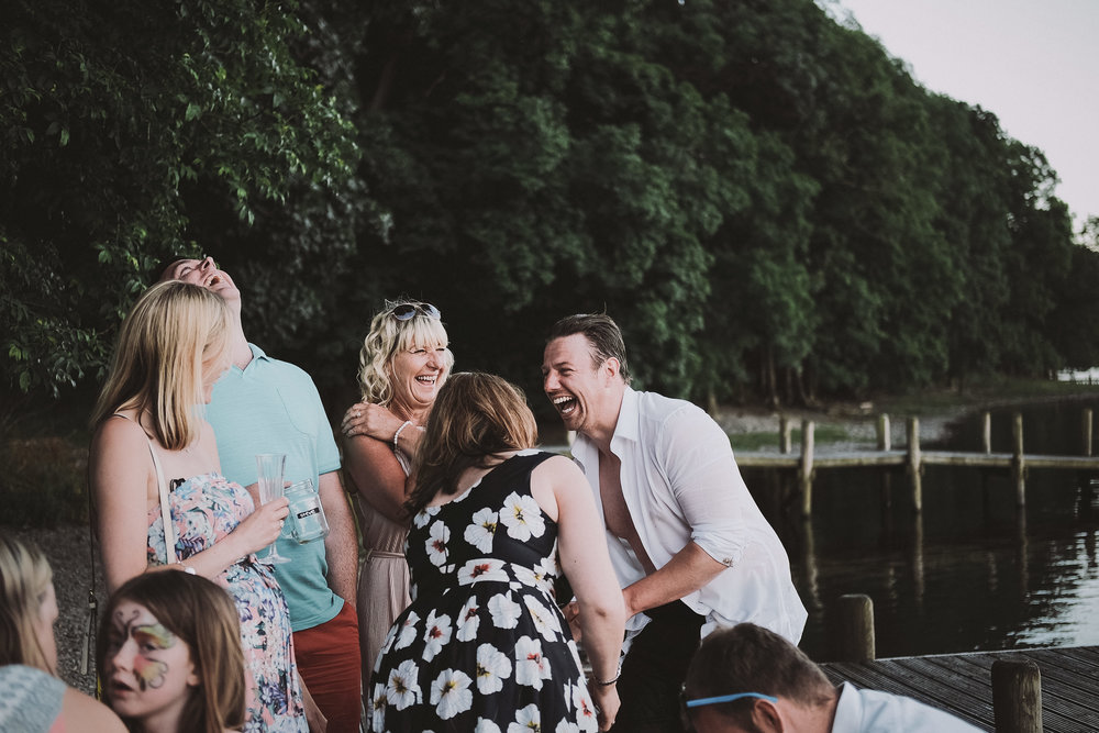 The groom laughs with guests after being thrown in Coniston water at Julia and Darren's Lake District wedding by Barry Forshaw