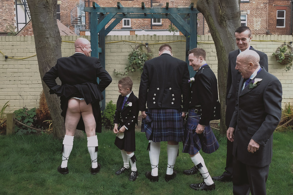 A groomsman lifts up his kilt as the rest of the groomsmen look on and laugh