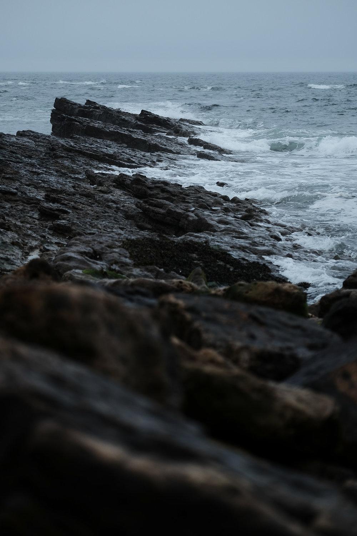 Stormy seas break on jagged rocks on the Northumberland coast
