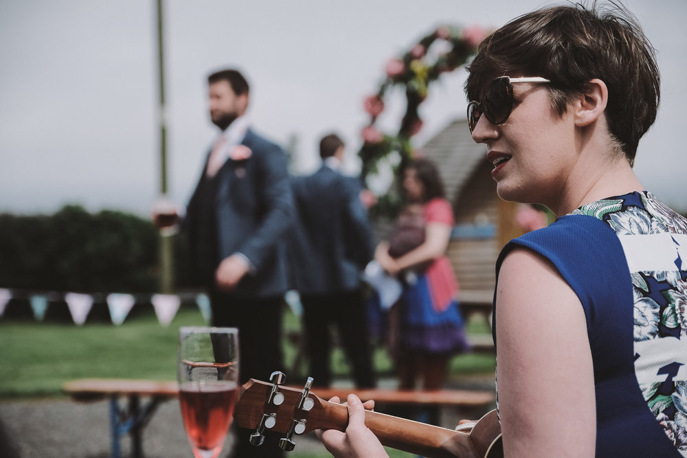 A guest plays ukulele for the entrance of the bride as the groom looks on