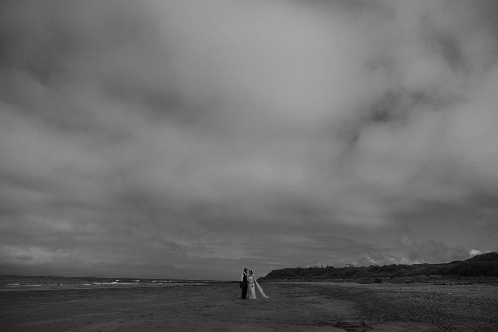 Black and white photo of the bride and groom walking along the beach under a vast sky