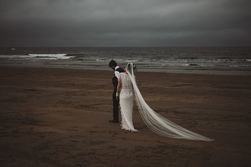 Bride and groom walk along a stormy beach in Northumberland