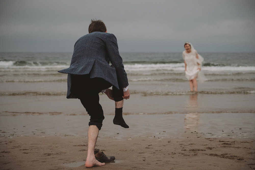 Groom takes off his socks to join his bride in the sea on the Northumberland coast