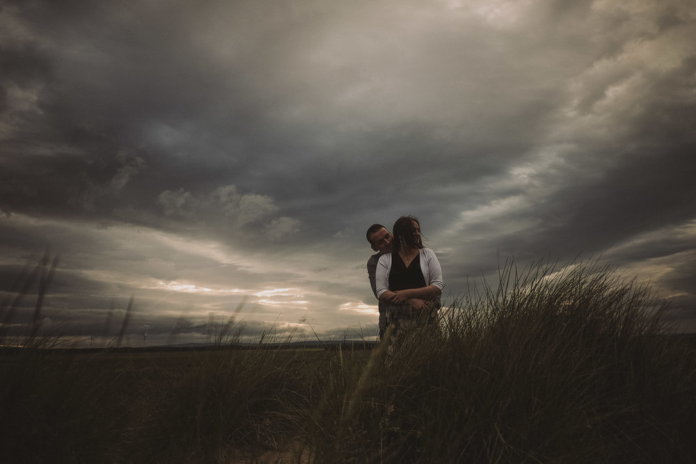 Engaged couple embrace underneath a stormy sky