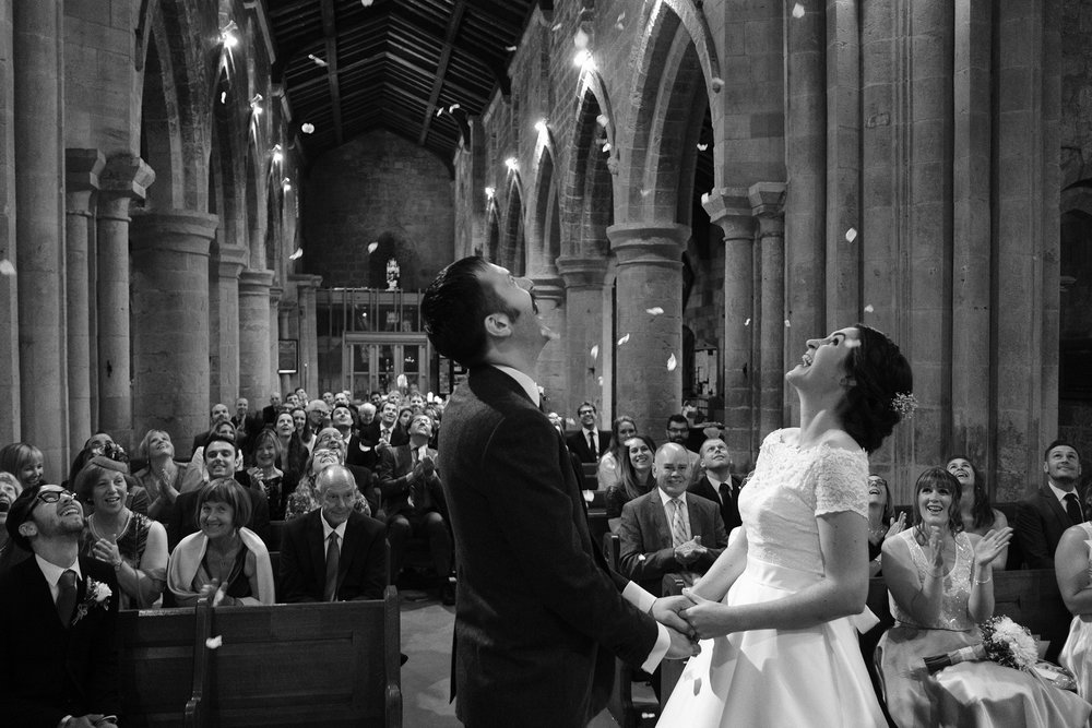 Black and white photo of the bride and groom being showered with confetti in the church