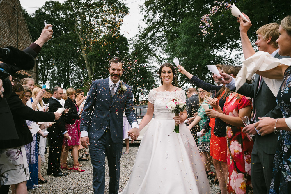 Colourful photo of the bride and groom being showered in confetti