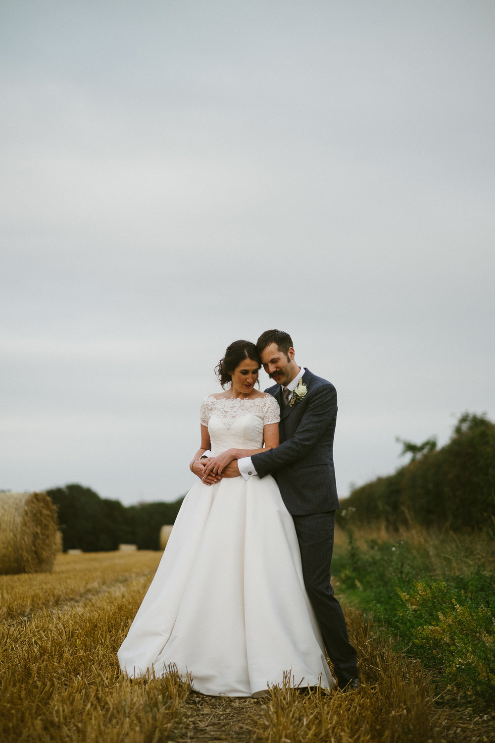 Bride and groom hold each other close in a farmers field in Yorkshire