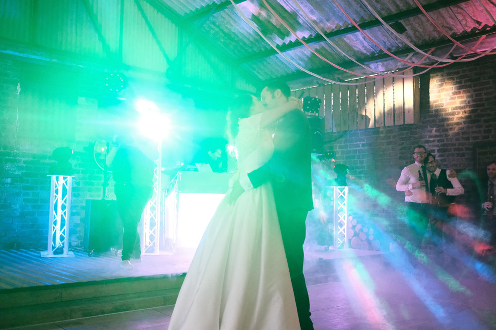 Bride and groom dance under disco lights while same sex couple cuddle in background