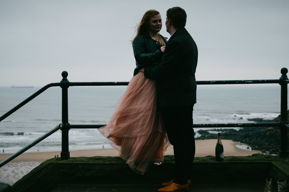 Moody engagement shot of couple cuddling in Tynemouth
