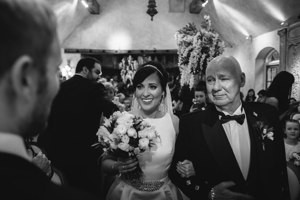 Black and white photo of bride walking down aisle with father at le petit chateau