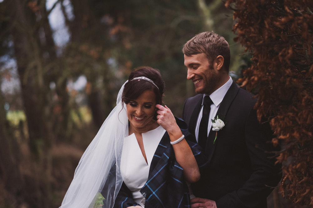 Bride and groom laugh in the grounds of le petit chateau northumberland