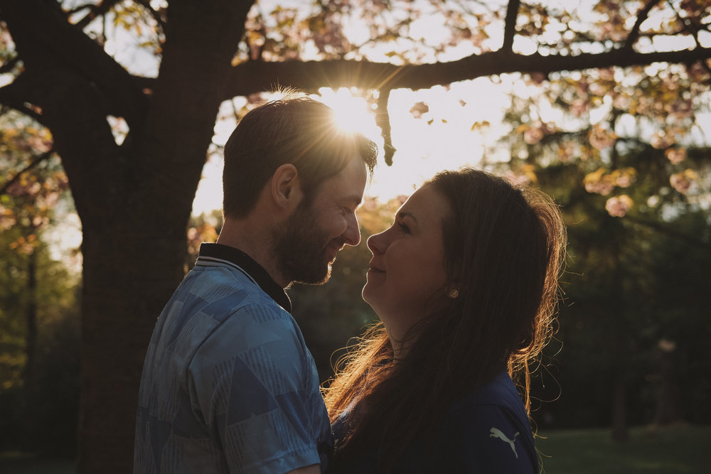 Couple kiss under trees while bathed in warm sunlight on engagement shoot