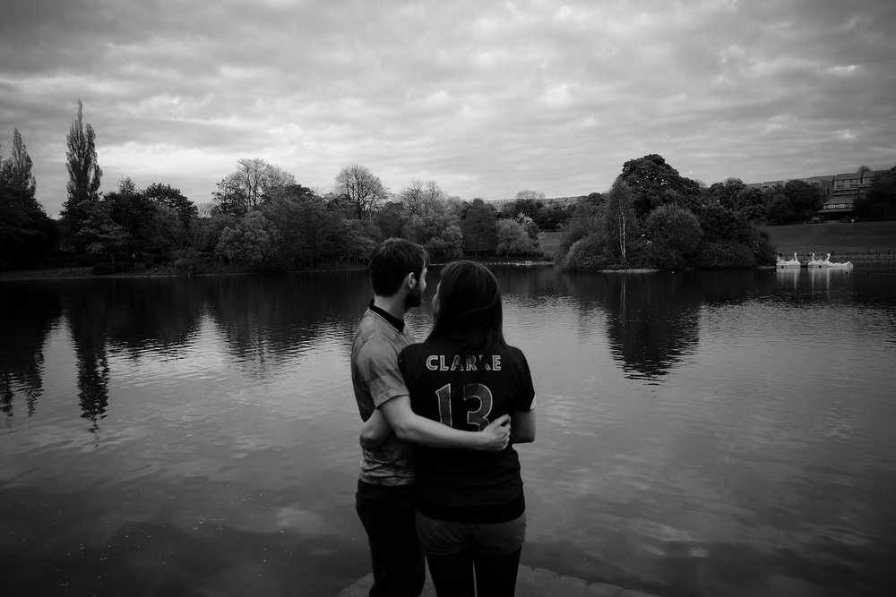 Black and white photo of couple cuddling in front of Saltwell Park lake