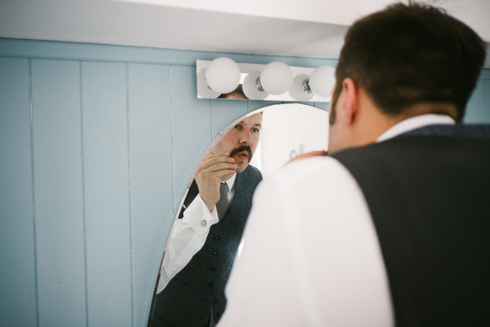 Groom waxes his moustache in front of mirror while getting ready for his wedding