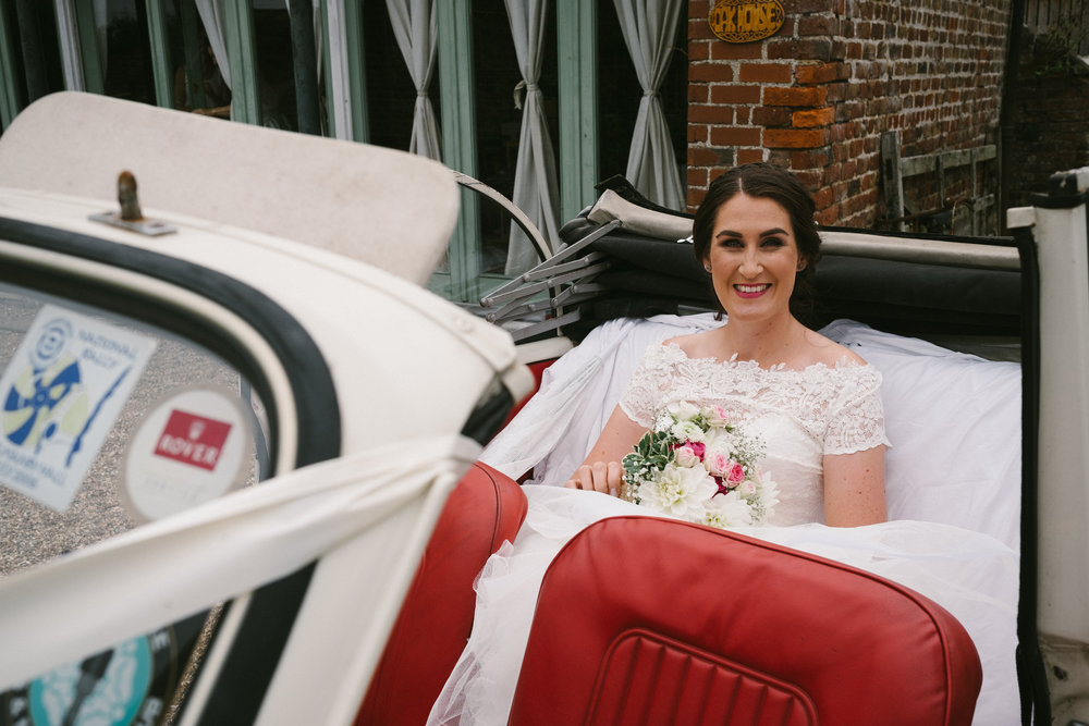 Bride smiles in back of open top car just before driving to church