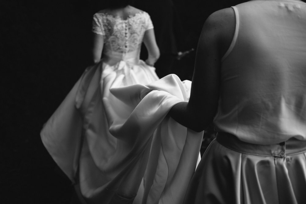 Black and white photo of the bride walking along a narrow path with the bridesmaid holding up her dress