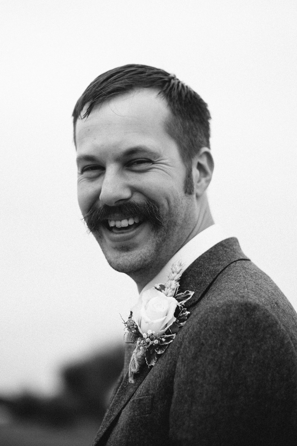 Black and white close up of the groom laughing