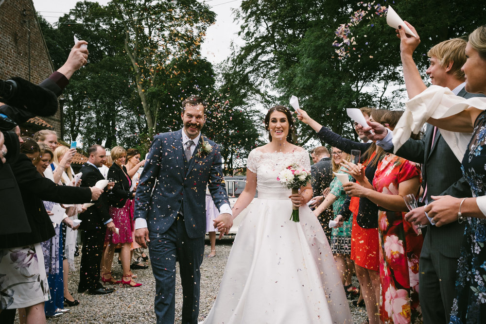 Bride and groom are showered in confetti by their guests