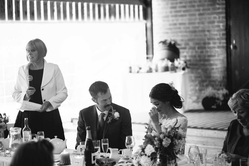 Black and white photo of the mother of the bride speech while the bride and groom listen