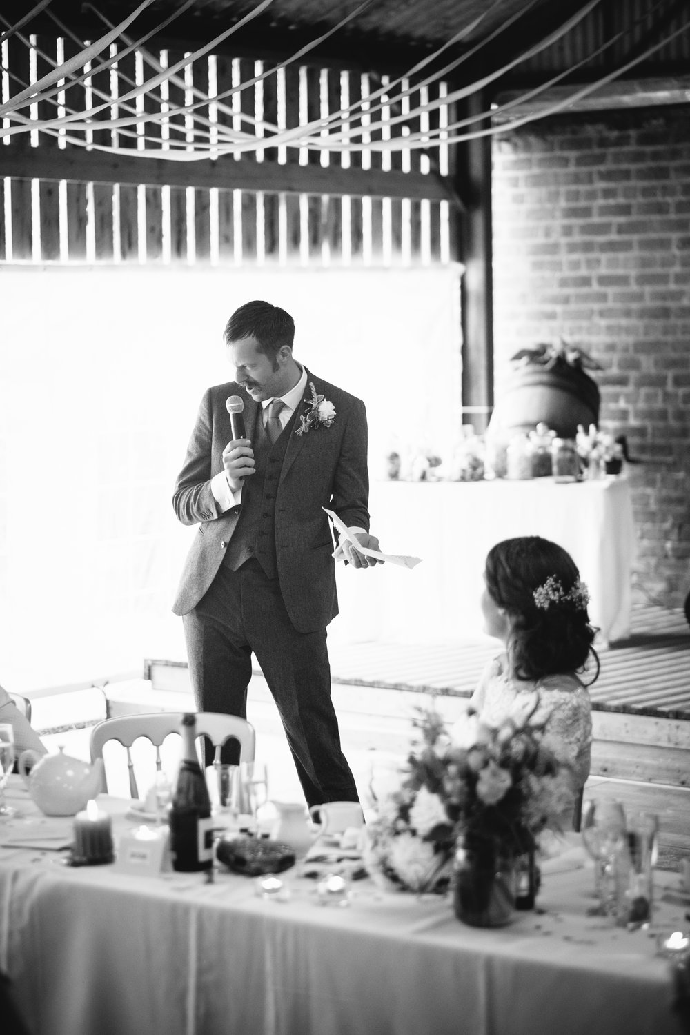 Black and white photo of the groom telling a joke during his speech