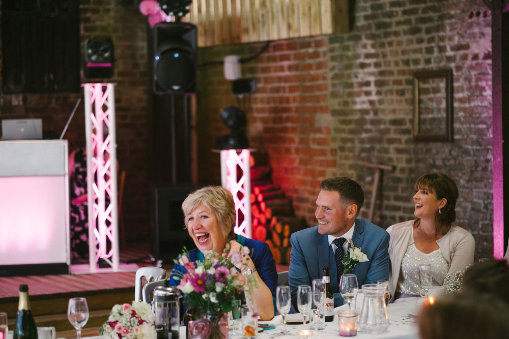 Family and guests laugh during the wedding speeches at Dale Farm