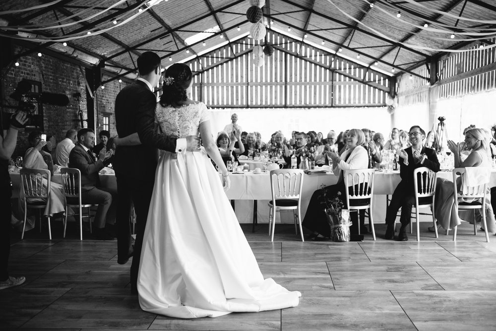 Black and white photo of the bride and groom cuddling while their guests look on