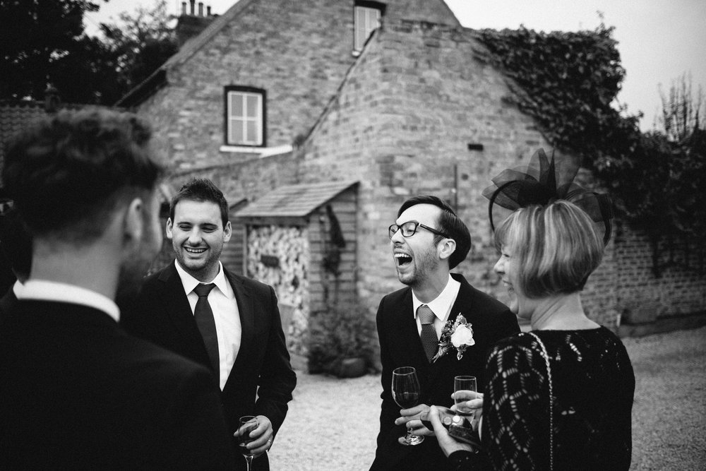 Black and white photo of the guests laughing at Dale Farm