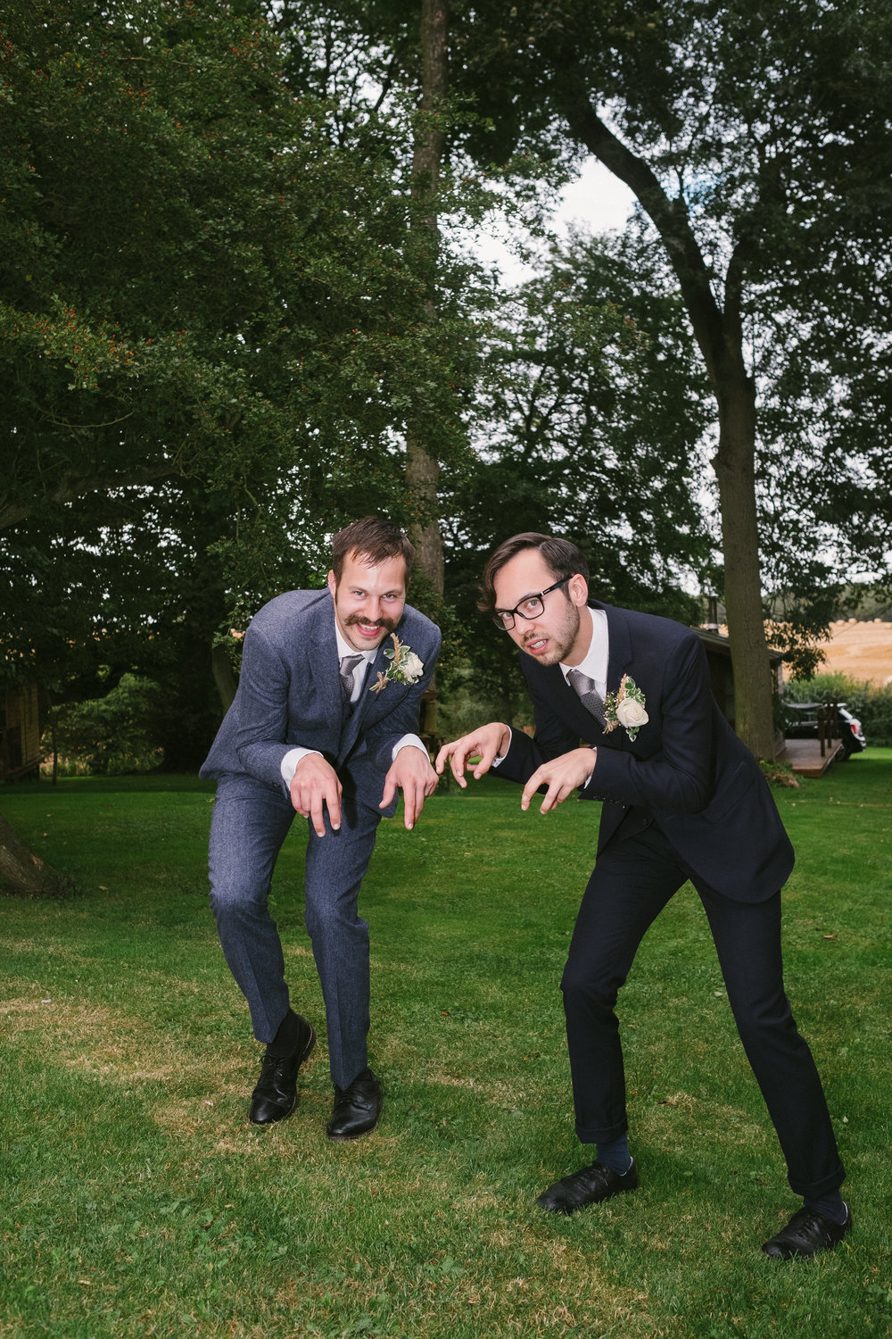 Groom and best man make dinosaur poses at Dale Farm