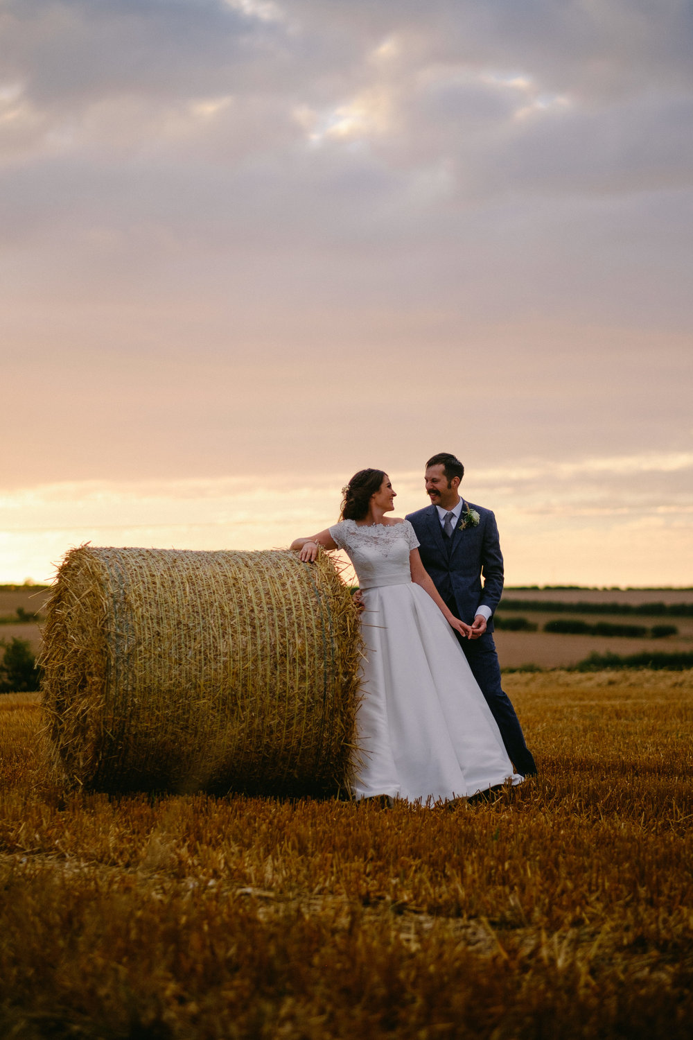 Bride and groom hold hands next to a hay bale with glorious sunset behind