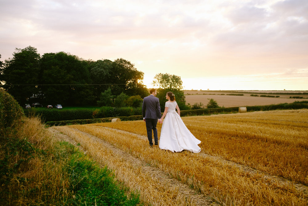 Bride and groom walk through wheatfield holding hands with warm sunset behind