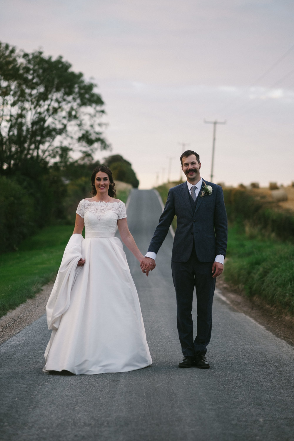 Bride and groom hold hands on road at Yorkshire Wedding