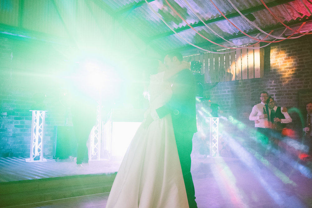 Bride and groom illuminated by disco lights dance while guests look on