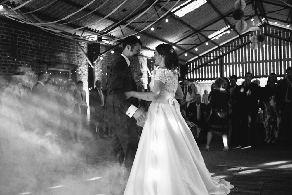 Black and white photo of the first dance with bride and groom wreathed in smoke
