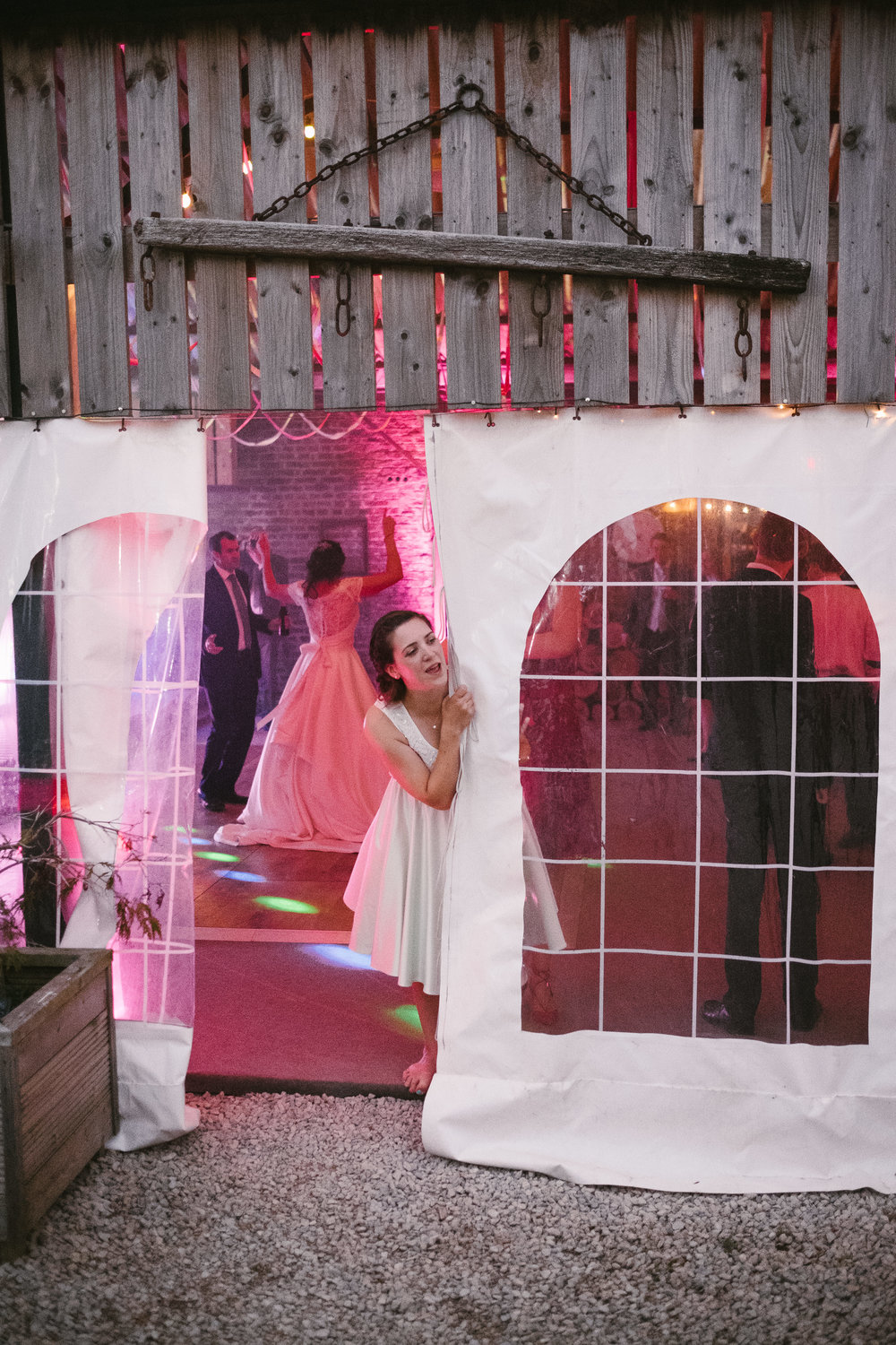 Bridesmaid peeks out of marquee while bride dances in the background