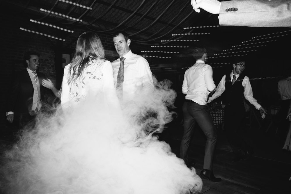 Black and white photo of the guests dancing in smoke at Dale Farm