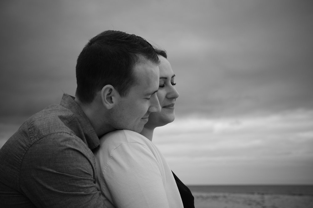 Black and white photo of couple holding each other close with eyes closed on Northumberland coast