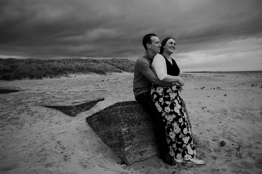 Black and white photo of couple sitting on tank trap at beach in Northumberland