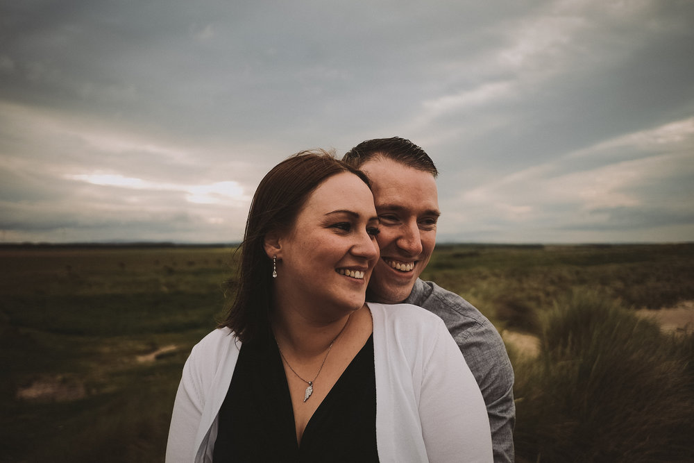 Couple smiling and laughing on engagement shoot at coast