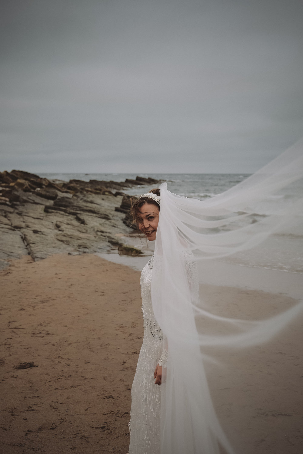 Bride smiles as her veil is caught by the wind
