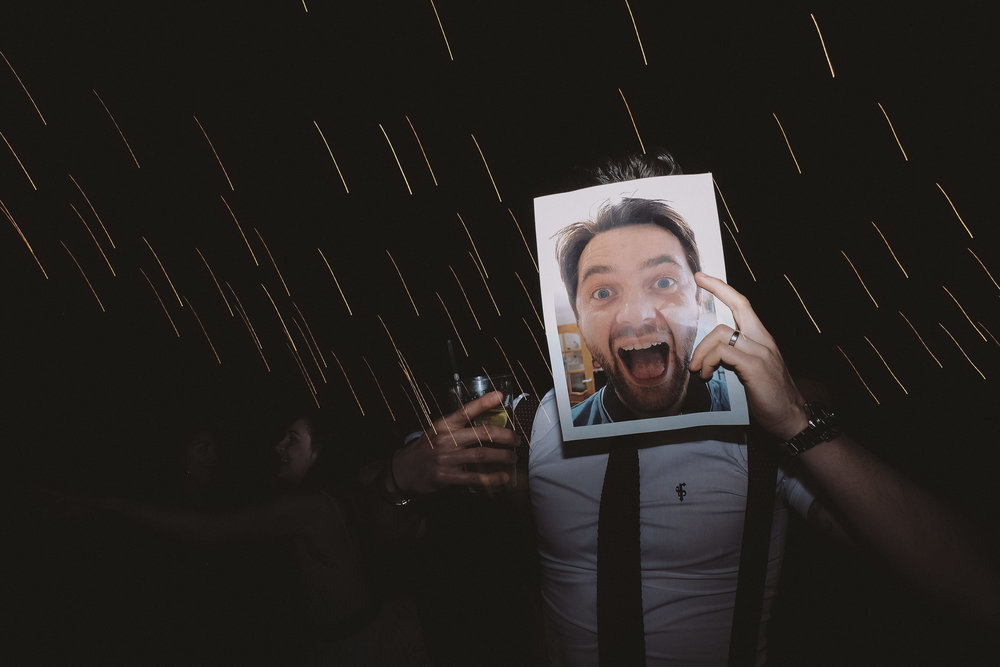 Wedding guest poses with photo of grooms face over his own